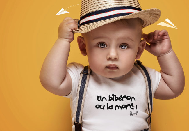 Cute baby boy posing in summer hat on yellow background. Adorable little child in studio.